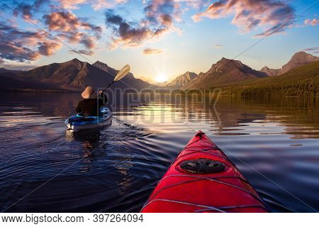 Adventurous Man Kayaking In Lake Mcdonald With American Rocky Mountains In The Background. Colorful