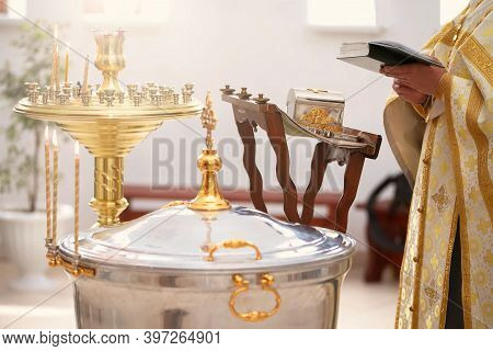 Baptism Rite. Font For Orthodox Baptism And The Priest Reads A Prayer.