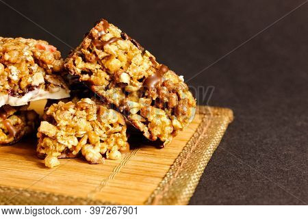 Energy Bars With Muesli, Nuts And Dried Fruit On A Black Background. Close-up, Selective Shot.