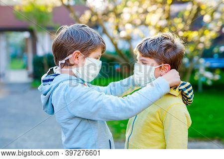 Kid Boy Helping Brother To Put Medical Mask On Face As Protection Against Pandemic Coronavirus Disea