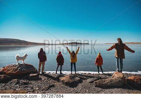 Group Of Five Young Friends With White Husky Dog Are Having Rest And Looking At Mountain Lake. Altai
