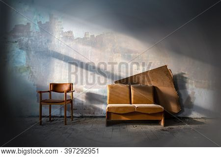 Old Leather Couch In Abandoned Factory Building Side Lit By Sun. Rustic Furniture In Haunted House