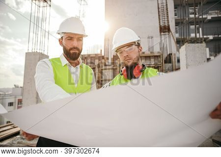 Serious Male Architect And Engineer In Hardhats Analyzing And Discussing Blueprint While Working Tog