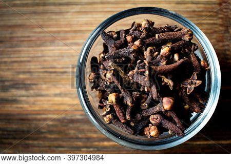 Dried Cloves In A Bowl Over Wooden Background. Spice Clove For Favouring.