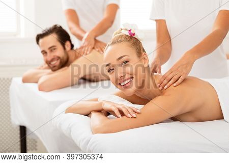 Married Couple Receiving Back Massage Together At Spa Salon, Smiling To Camera. Wellness, Beauty Tre