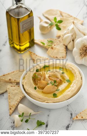 Roasted Garlic Hummus Topped With Olive Oil And Garlic Cloves