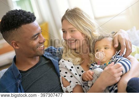 Young parents cuddling 8-month baby girl
