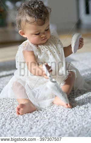 Cute dressed-up baby girl sitting on carpet floor at home