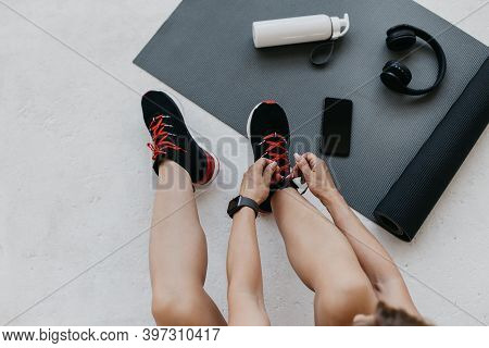 Preparing For Morning Workout At Home Or Gym. Lady Athlete Ties Shoelaces On Sneakers, Sits On Floor