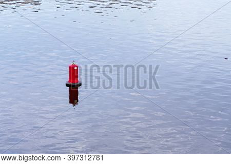 Floating Red Navigational Buoy On Blue Water Of Dnipro River. Buoy In The River. Navigation Equipmen