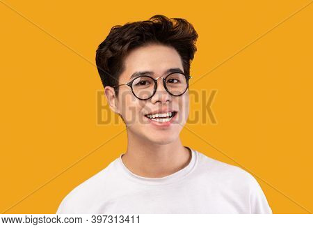 Close Up Headshot Portrait Of Smiling Young Asian Man Wearing Stylish Eyeglasses, Looking At The Cam