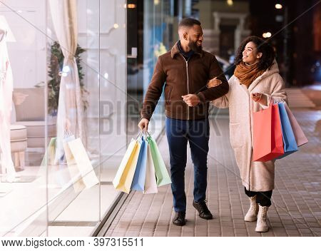 Family Shopping Concept. Full Length Portrait Of Happy Black African American Couple Walking Down Th