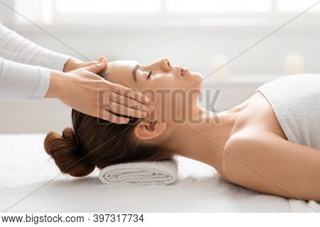 Unrecognizable Spa Attendant Massaging Relaxed Lady Head, Closeup. Attractive Young Woman Having Rel