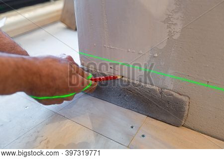 Builder Works With A Laser Construction Level In The Apartment That Is Under Construction, Remodelin