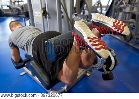 sport, fitness and bodybuilding concept - man exercising and flexing muscles on leg curl machine in gym