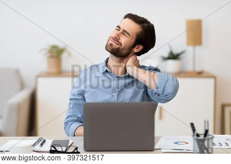 Man Touching Aching Neck Working On Laptop Computer Sitting At Workplace In Modern Office. Health Pr