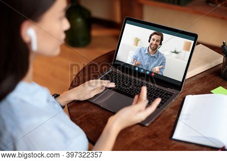 Distant Communication Concept. Over The Shoulder View Of Woman In Earphones Having Video Conference
