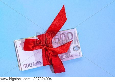 Euro Banknotes Five Hundred On A Stack With Red Bow On A Blue Background. Gift, Bonus Or Reward Conc