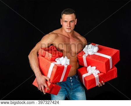 Sexy Muscular Man Holding Christmas Gifts. Santa Claus Has Surprise For You. Naked Man With Sexy Rip