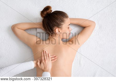 Top View Of Young Lady Having Healing Full Body Massage From Unrecognizable Female Therapist At Luxu