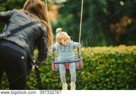 Blonde Haired Girl On The Swing In Center