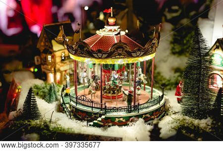 Carousel In European Christmas Fair Miniature Toy. Winter Christmas Eve Scene With Traditional Minia
