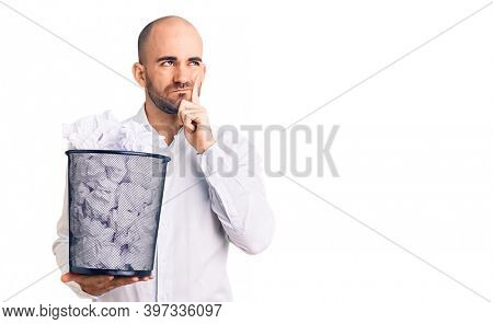 Young handsome man holding paper bin full of crumpled papers serious face thinking about question with hand on chin, thoughtful about confusing idea