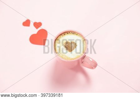 Pink Mug Of Cappuccino Coffee With A Heart Of On Foam And Red Hearts Valentines On A Pink Background