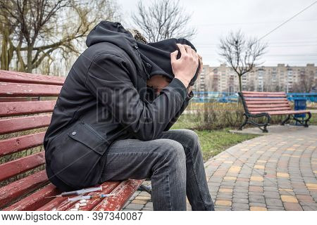 Drug Abuse Concept. Addict In The Hood Sitting On A Bench In The Park. Life Style