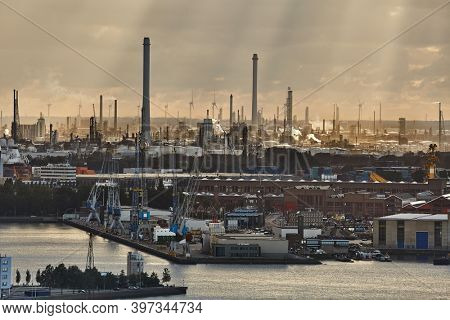 Huge industrial docks area with of Rotterdam refineries and wind power turbines