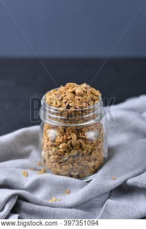 Crunchy Honey Homemade Granola With Nuts, Berries, Chocolate In A Glass Jar On A Dark Concrete Backg