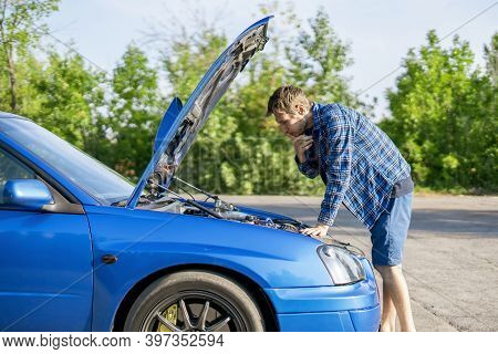 The Sad Disappointed Man Standing Near The Car With Opened Hood, Fix Some Problems With Engine