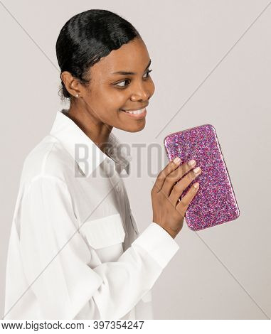 Happy black woman showing a glittery pink clutch bag
