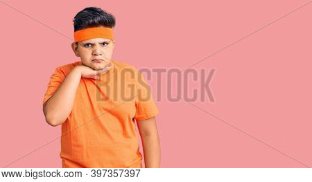 Little boy kid wearing sportswear cutting throat with hand as knife, threaten aggression with furious violence