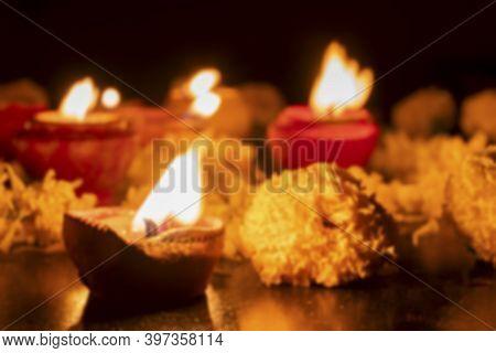 Blurred Image Of Very Low Angle View Of Rangoli Flowers And Candles Or Diyas, Deepawali Lights At Ni