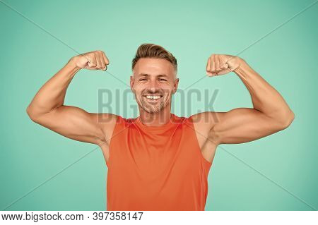 Stay Strong In Your Life. Happy Athlete Show Physical Strength. Strong Man Flex Arms Blue Background