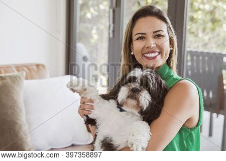 Portrait Of Beautiful Brazilian Woman And Her Pet Shih Tzu Dog Looking At Camera At Home, Making Ved