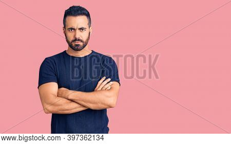 Young hispanic man wearing casual clothes skeptic and nervous, disapproving expression on face with crossed arms. negative person.