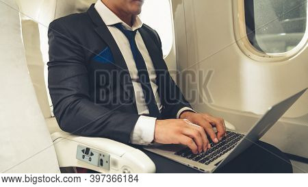 Young Businessman Using Laptop Computer In Airplane . Business Trip Travel Concept .