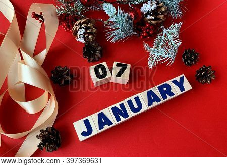 January 7 On Wooden Cubes.near Fir Branches, Cones, Ribbon, Gift Box On A Red Background.beginning O