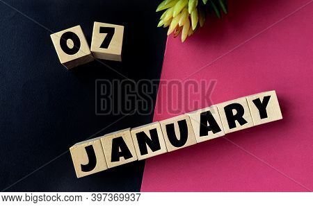 January 7 On Wooden Cubes On A Black And Pink Background.beginning Of Year .calendar For January.