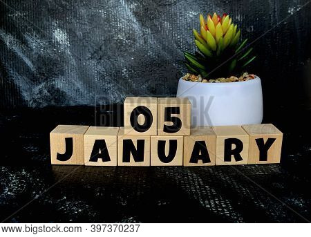 January 5 On A Black Background On Wooden Cubes .next To It Is A Pot With A Flower .calendar For Jan