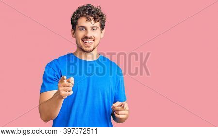 Young handsome man with curly hair wearing casual clothes pointing fingers to camera with happy and funny face. good energy and vibes.