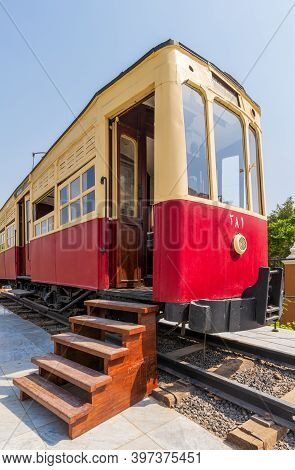 Exterior Of Vintage Tram With Wooden Stairs Near Open Doors Located On Rails On Sunny Day On Town St