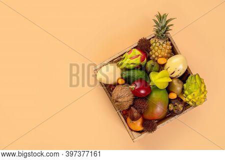 Assortment Of Tropic Fruits In Box Top View. Fruit Dragon, Papaya, Maracuya, Kiwi, Mango And Granadi