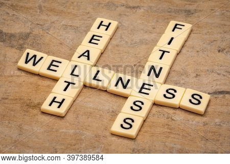 health, fitness and wellness crossword in ivory letter tiles against textured handmade paper, well being and lifestyle concept