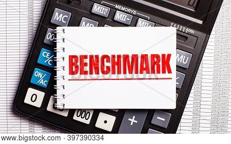 On The Table Are Reports, A Calculator And A Card With The Word Benchmark On It. Business Concept