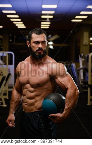 Strong Bearded Man With Medicine Ball In Fitness Sport Gym At Night