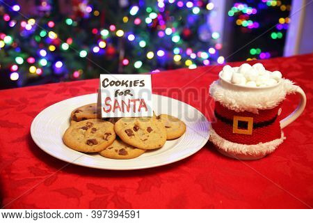 Cookies for Santa Claus. Fresh Baked Cookies and Hot Chocolate with Marshmallows left on a table for Santa Claus. A gift for Santa on Christmas Eve.