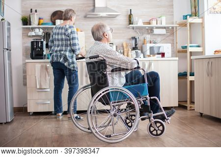 Pensive Disabled Man In Wheelchair Looking Through Kitchen Window While Wife Is Unpacking Food From